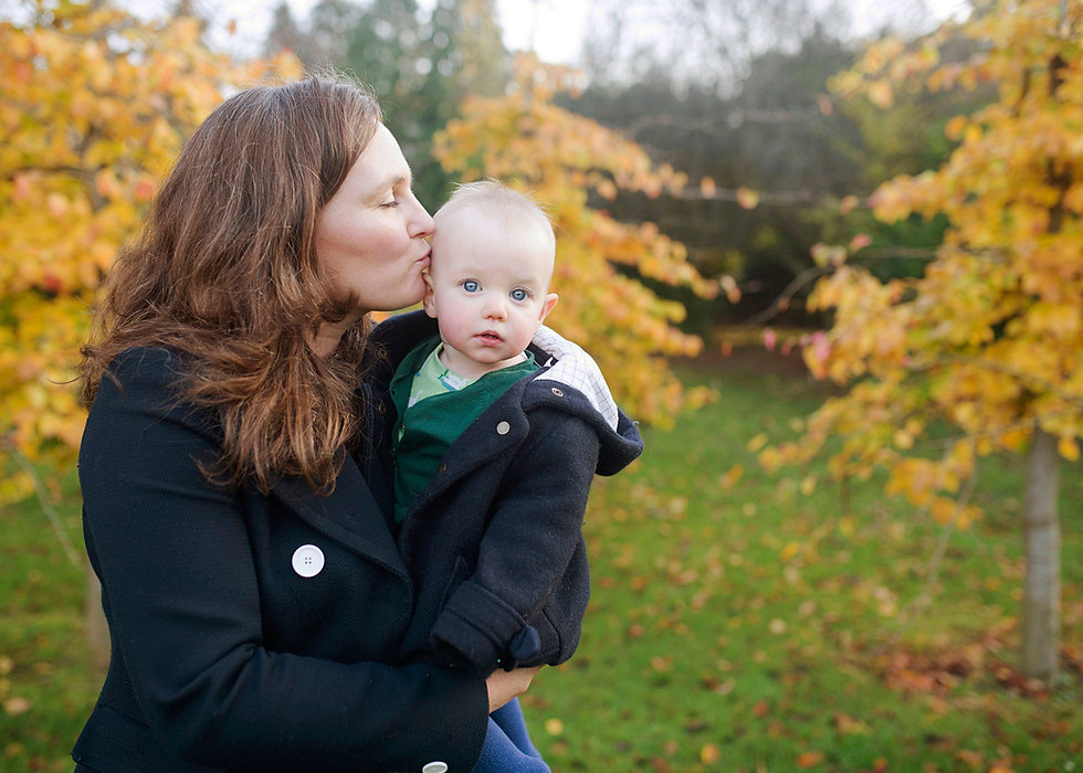 mother holding baby girl with an autumn backdrop