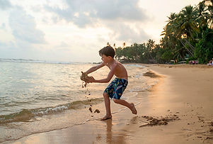 boy on a beach in Sri-Lanka playing with sand