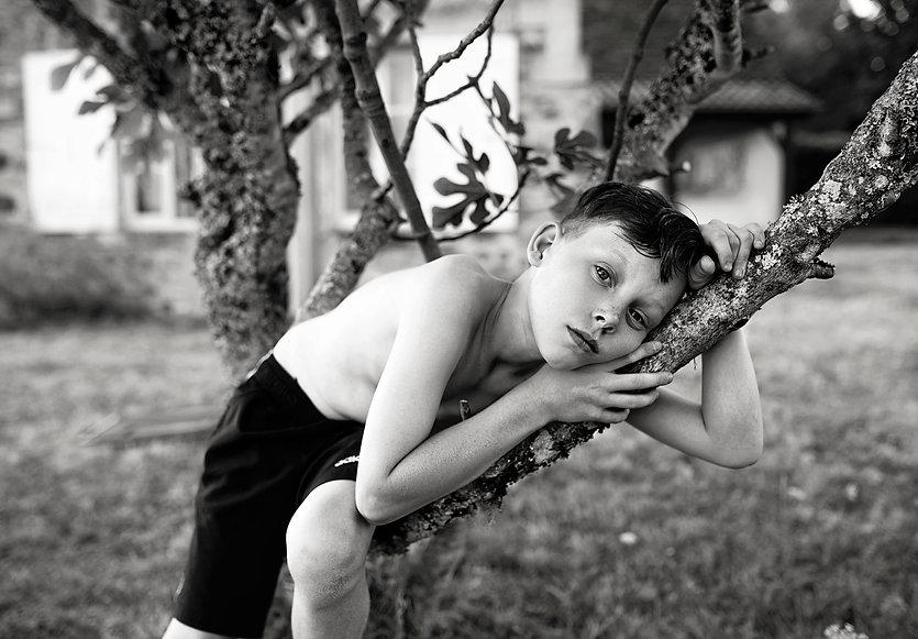black & white award winning portrait of a boy in a fig tree