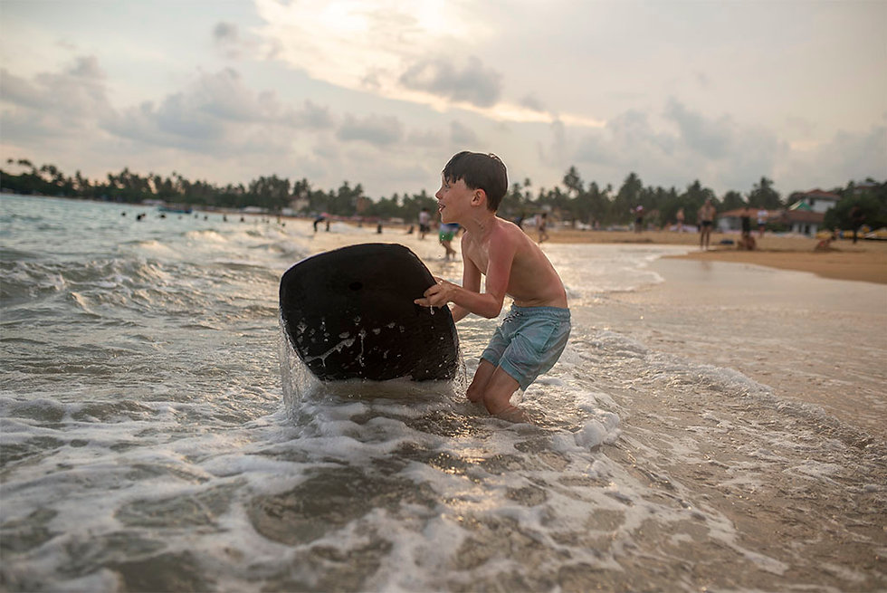 lifestyle photo of a boy in the waves with a suf board