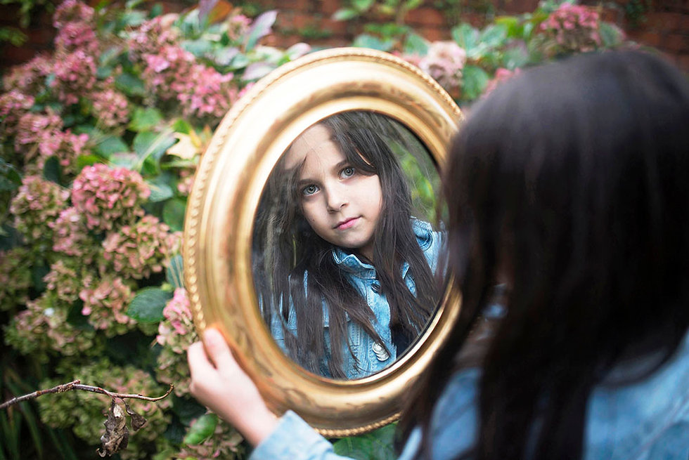 portrait of a girl looking into a mirror