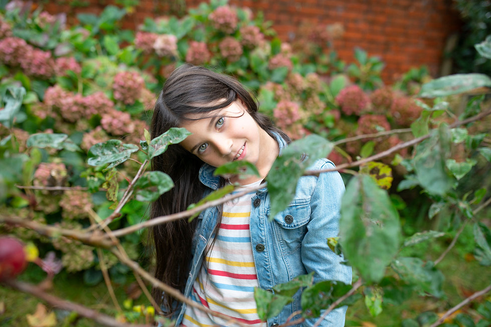 portrait of a dark haired child in a colorful garden