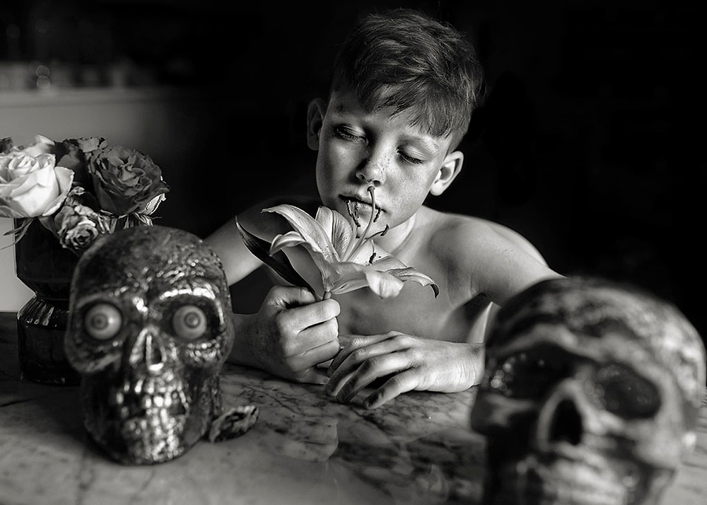 black & white Halloween portrait of boy with flowers and skulls