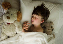boy sleeping in bed with soft toys