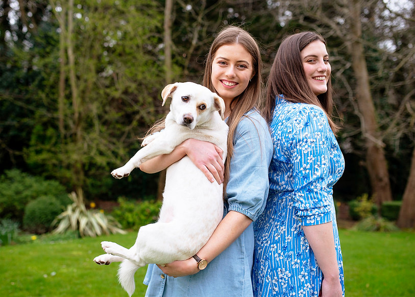 sisters holding a white dog