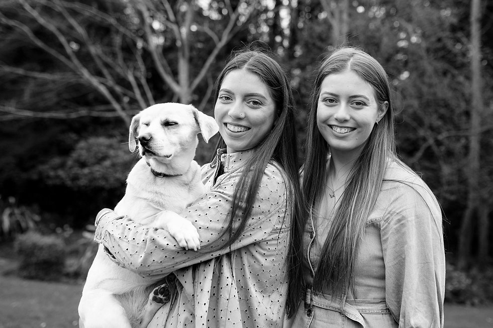 black & white family portrait of sisters holding a white dog