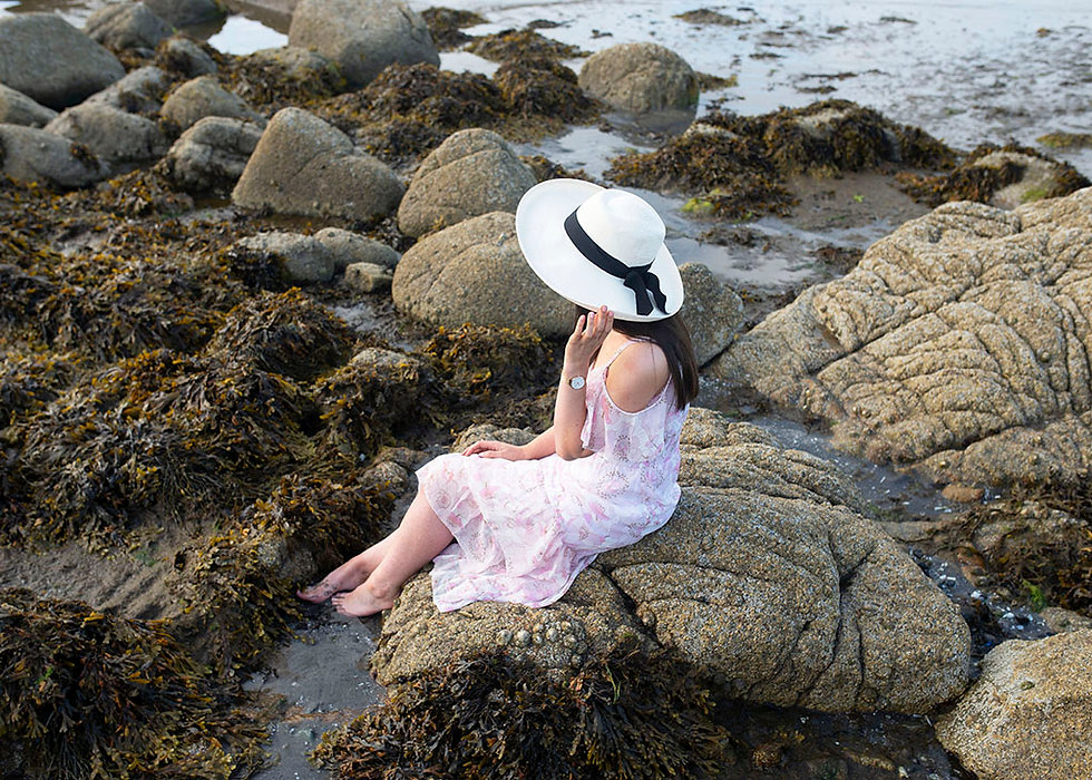 young woman with white hat sitting on rocks, rocky beach