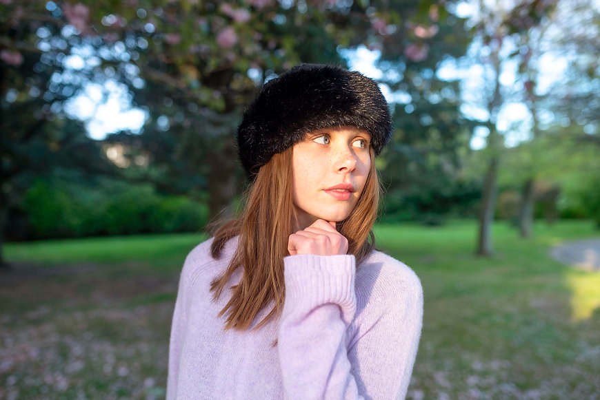 portrait of a girl in fake fur hat under cherry blossom