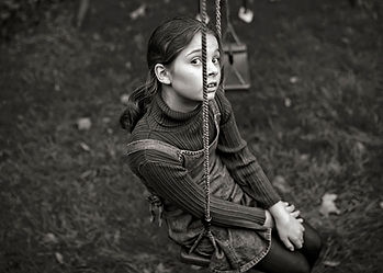 black & white portrait of a girl on a swing