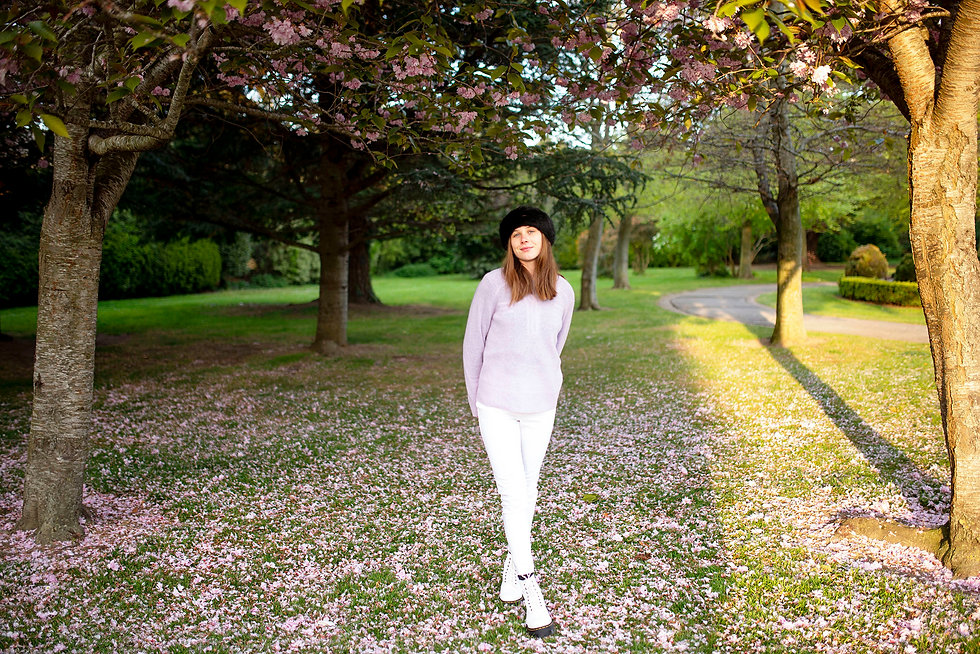 beautiful young lady wearing a pink jumper among pink cherry blossom