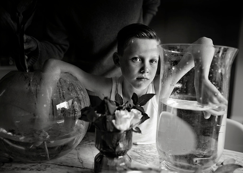 black & white fine art portrait of boy with vases
