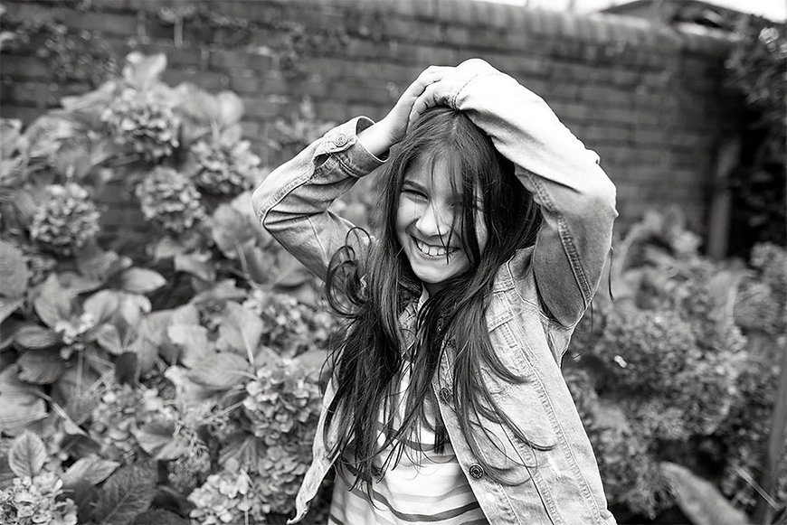 black & white portrait of a girl laughing