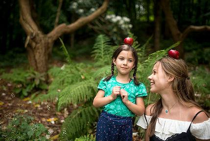 girl balancing apple on head, older sister laughing