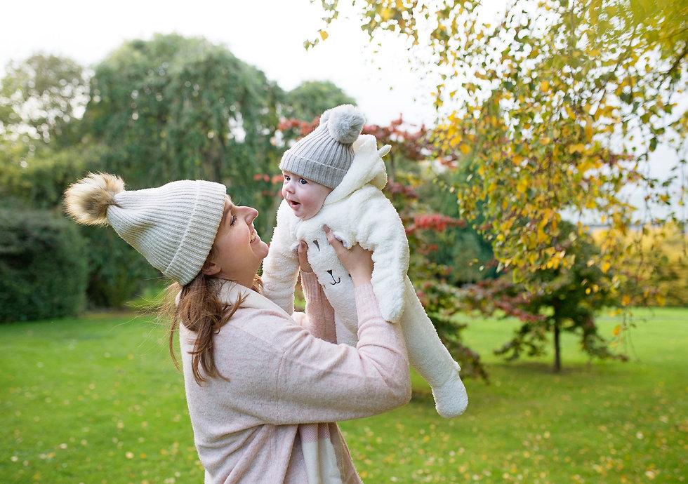 mum swinging baby in dublin park in autumn