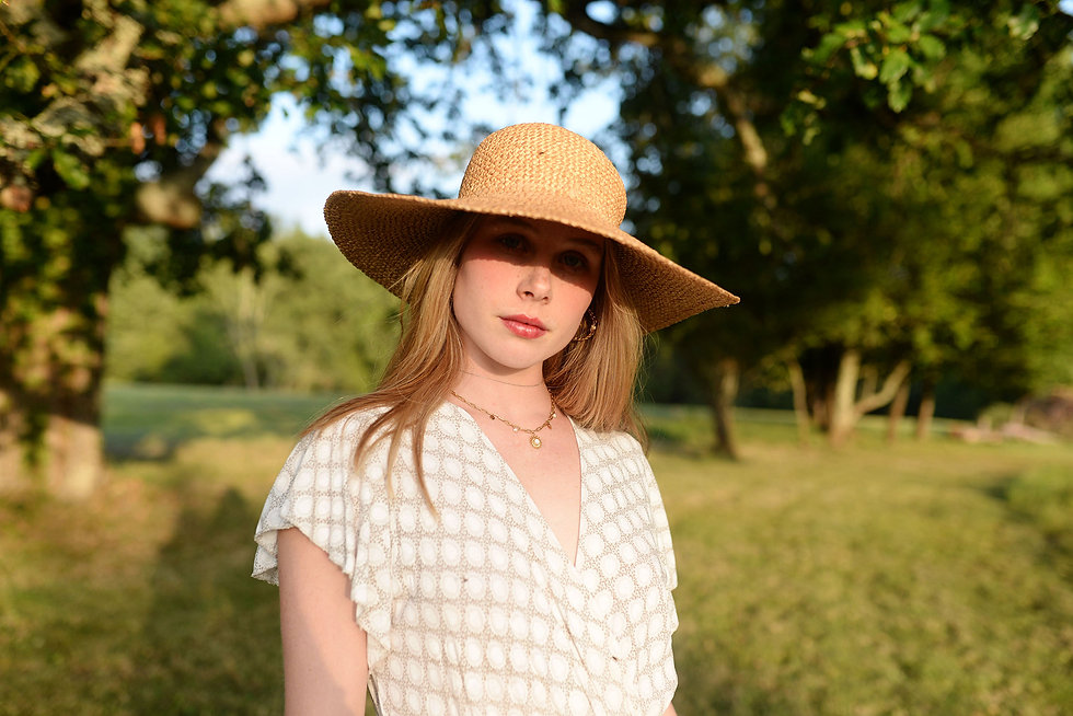 girl in golden light with straw hat
