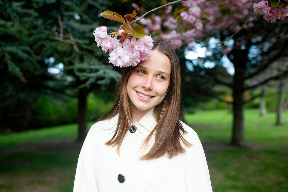 portrait of a girl smiling under a cherry blossom tree in a Dublin park