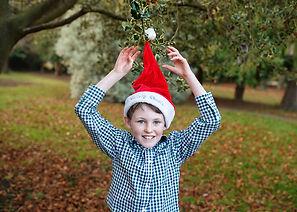 boy wearing a santa hat Christmas photoshoot