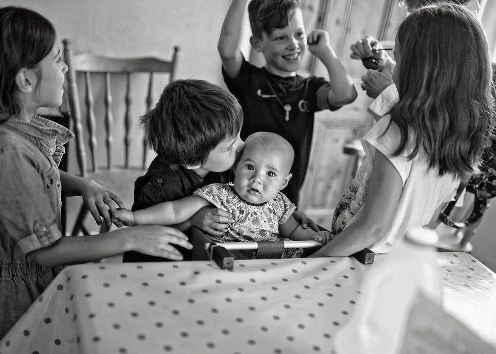 black & white portrait of children around a table and baby in a high chair