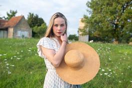 girl holding straw hat