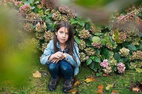 Girl sitting next to pink hydrangea bush