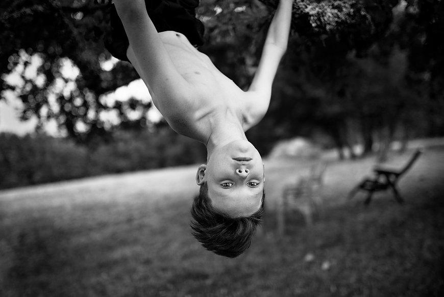 black & white fine art portrait of a boy hanging upside down from a tree