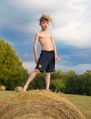 Boy standing on a haybale