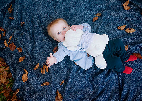 three month old baby holding a teddy bear