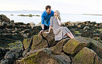 A couple sitting on a rock at Seapoint Dublin