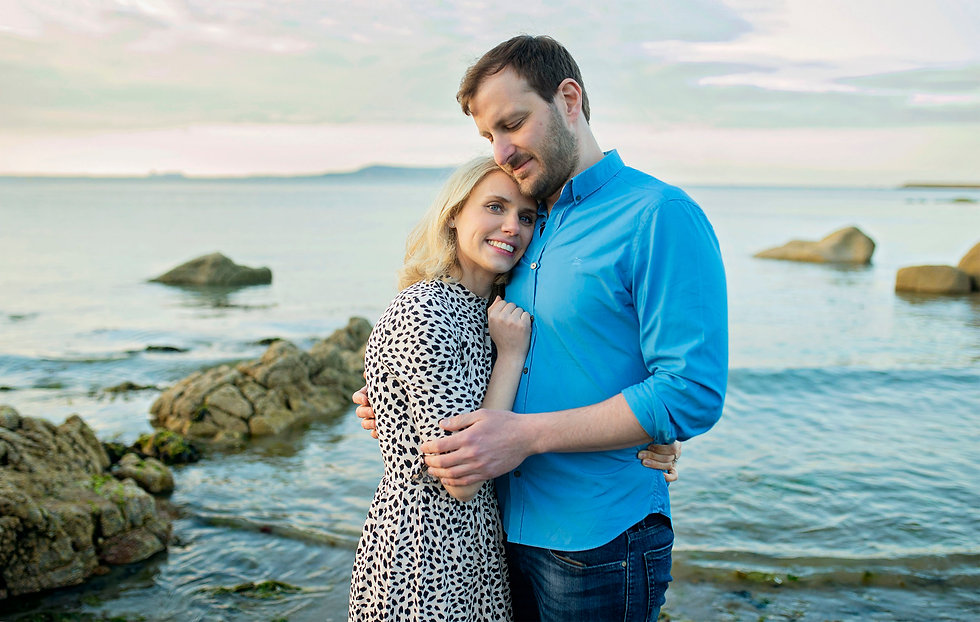 A portrait of a couple who are just engaged at the beach at Seapoint Dublin