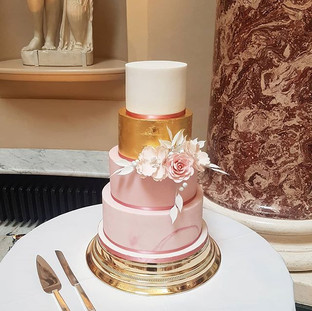 Four tier gold leaf and pink marble wedding cake with sugar flowers