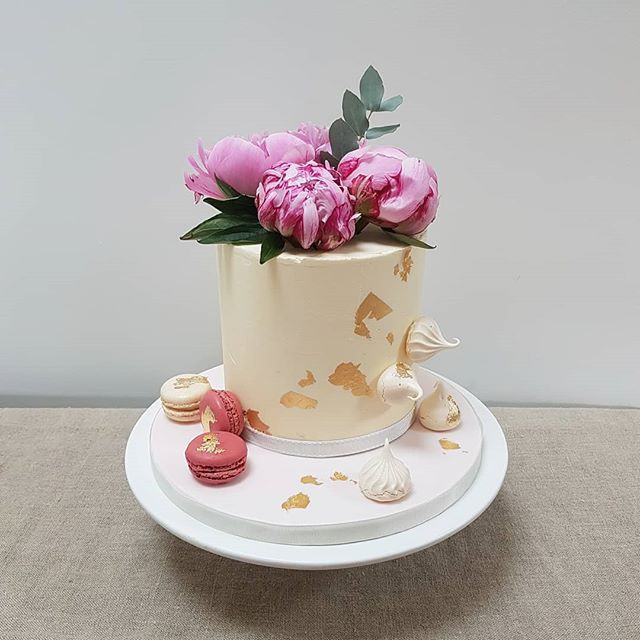 Buttercream cake with fresh peonies and gold leaf