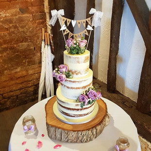 Semi naked wedding cake with lilac roses