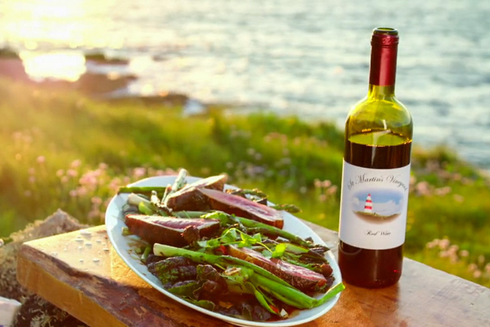 A wooden table with a place of freshly cooked food and a bottle of St Martin's wine on a clifftop with the sea behind