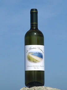 A bottle of St Martin's single variety Orion wine against a blue Scilly sky