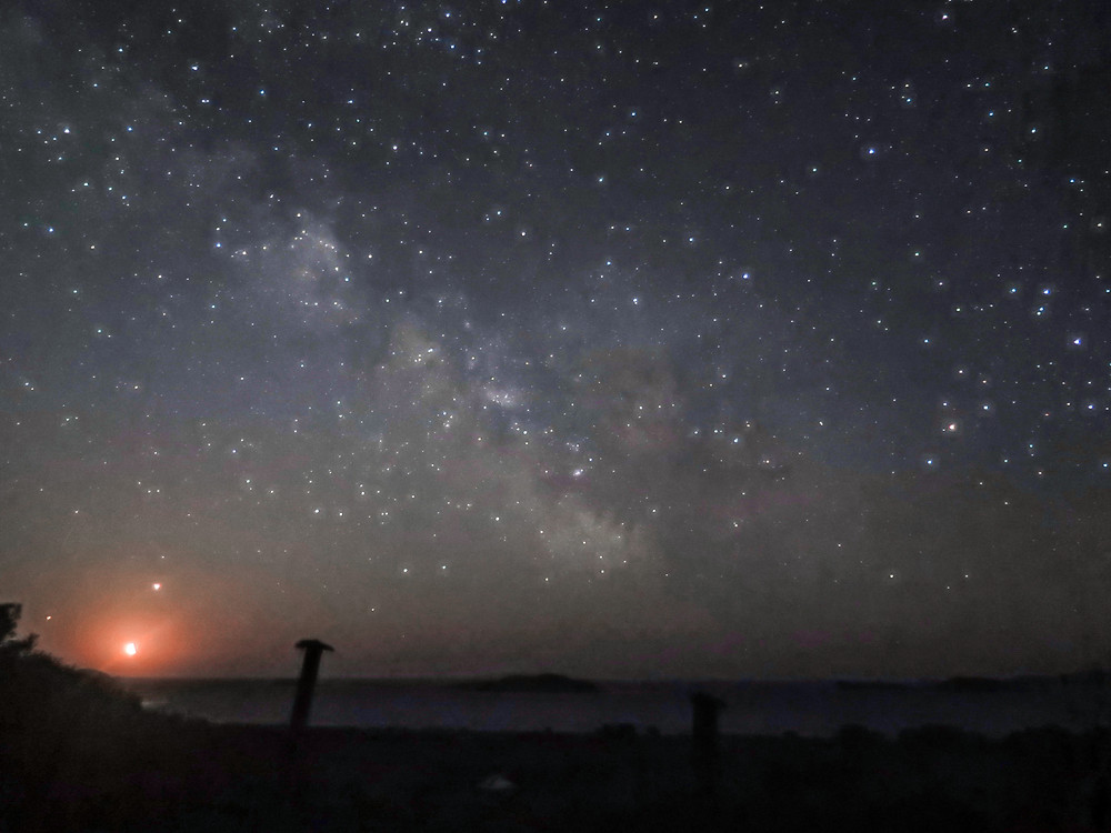 A dark starry sky with the milky way visible - below is the sea with island just discernable
