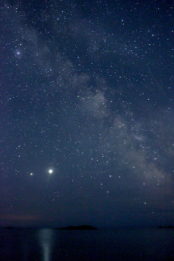 The stars above a dark sea with Jupiter bright and reflecting off the water, the milky way is visible