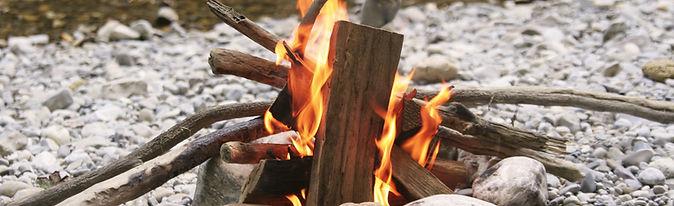 A campfire burns on rocks next to a creek.