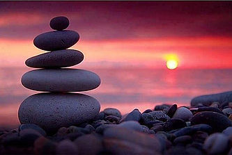Stacked rocks in front of water with beautiful sunset in background.