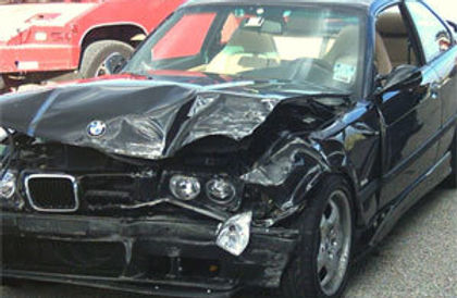 A black car with a damaged hood and front bumper is displayed.