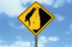 A yellow caution sign wth man falling off a cliff is displayed in front of a blue, cloudy sky.