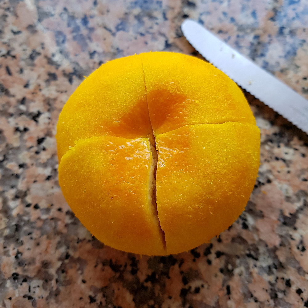 a cross is slit into the grated orange