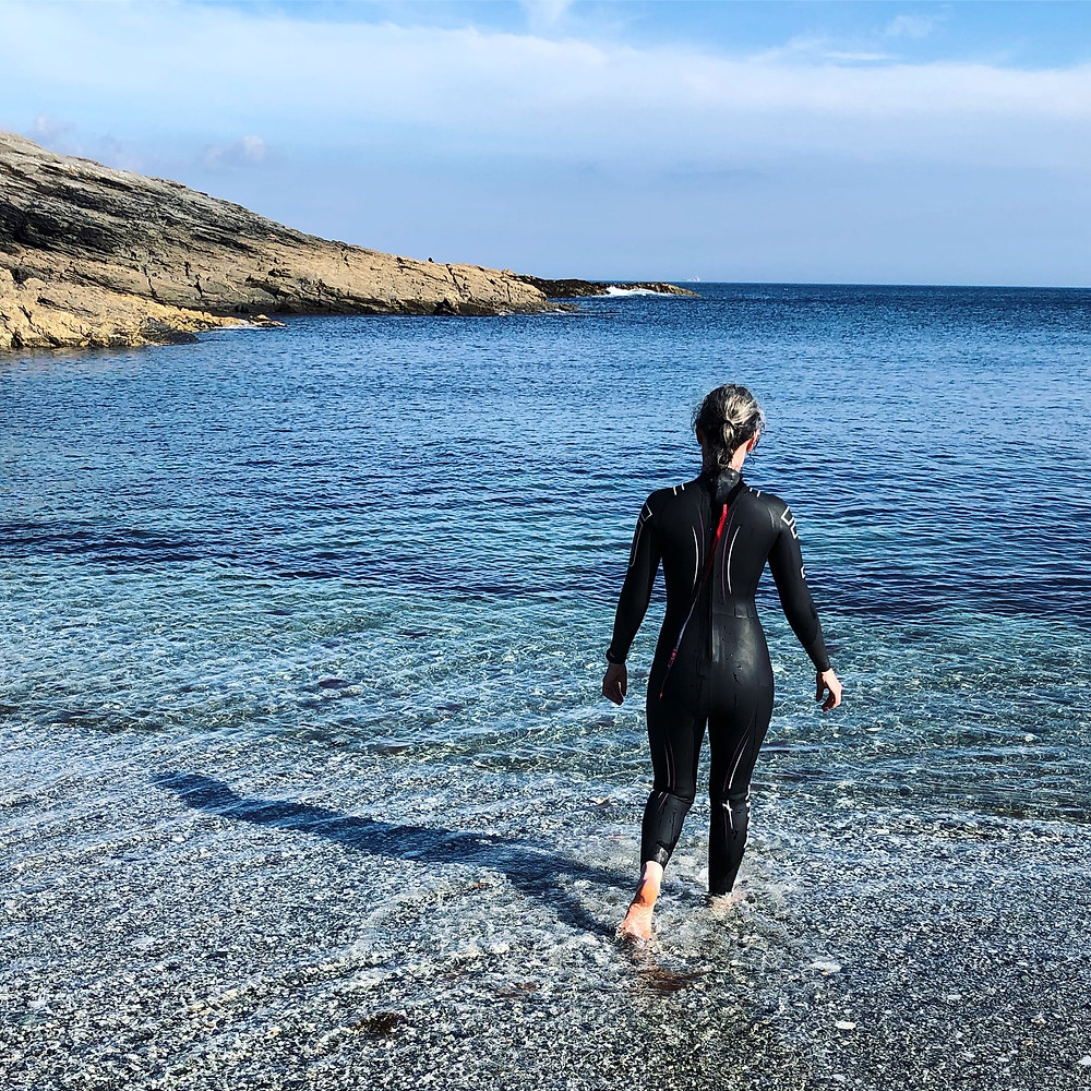 woman in a wetsuit walking into the sea