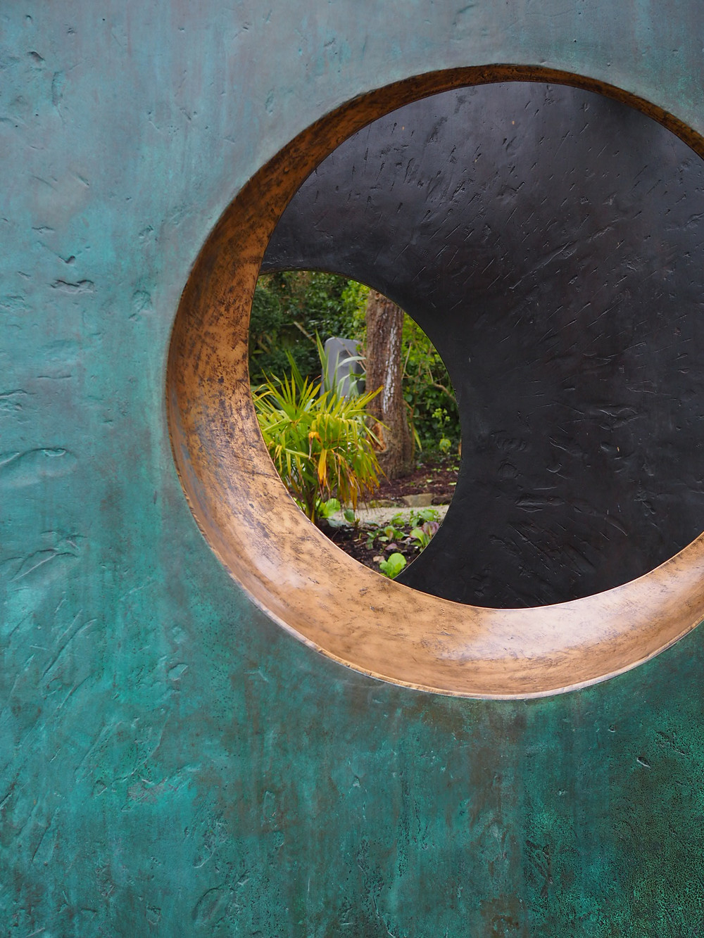 Looking through one of the bronze sculptures at The Barbara Hepworth Sculpture Garden near St Ives.