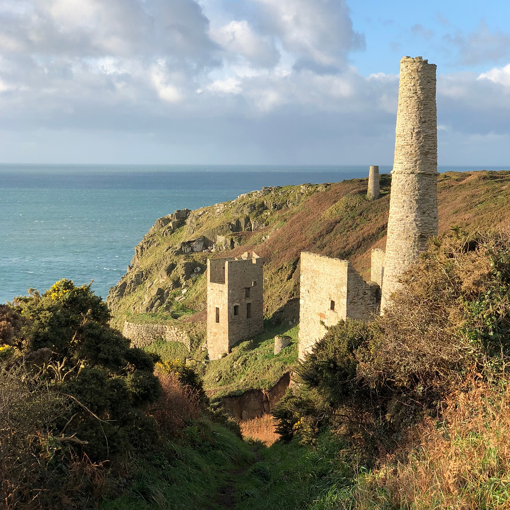 Ruined engine houses on the South West Coast Path near Rinsey, part of Cornwall's rich mining heritage