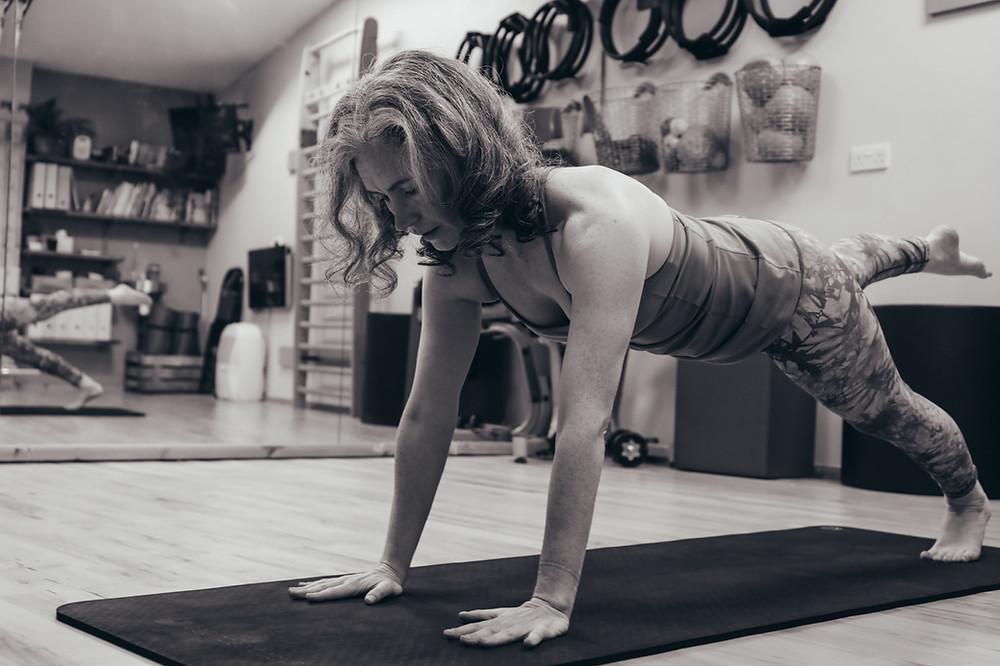woman performing Pilates mat work exercise