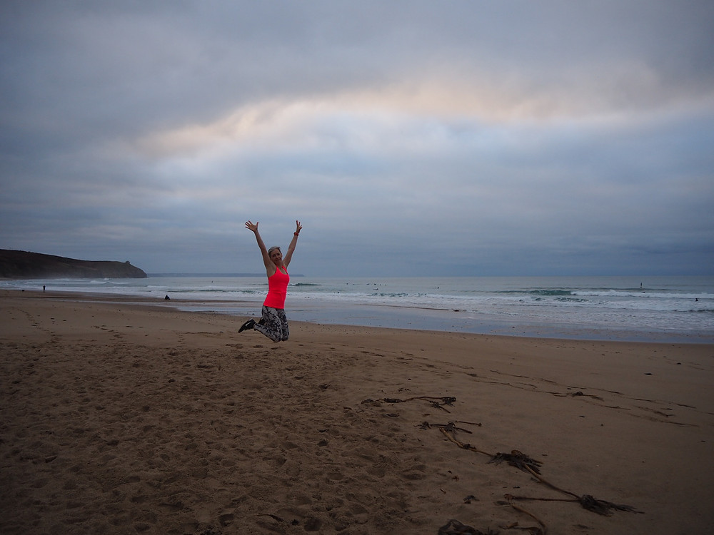 Woman jumping on beach in Cornwall