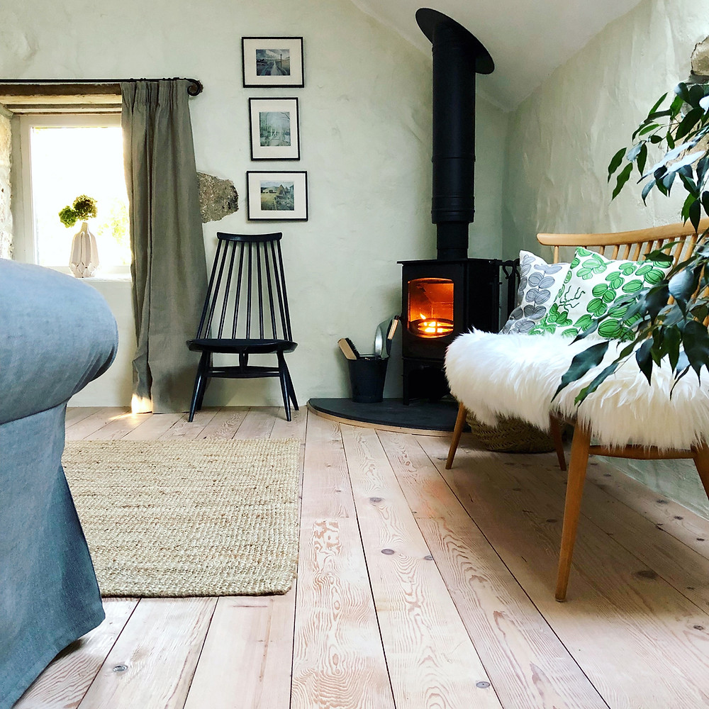 Mid-century furniture and a wood burning stove in Cornish cottage