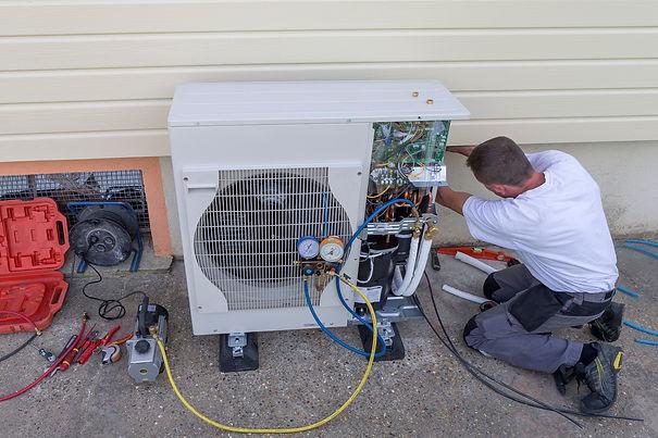 Installatör installerar utomhusdelen till en luftvärmepump.