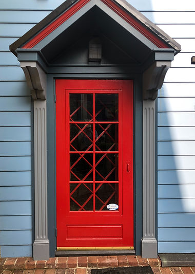 Red door with dark blue and grey trim leading to 122 W Cork St