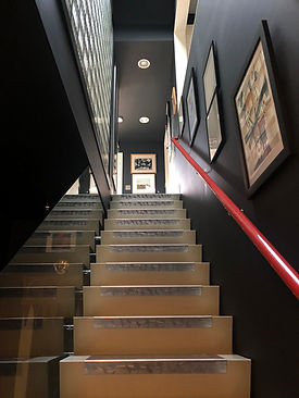 image of stairs leading upward with paintings on the side at the Peter Bullough Foundation